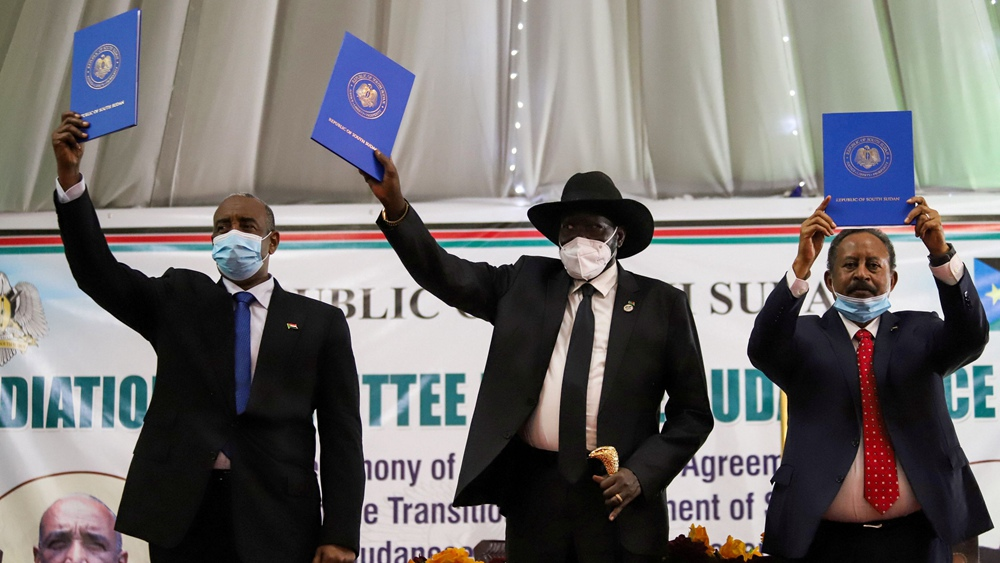 Sudan's Sovereign Council Chief General Abdel Fattah al-Burhan (L), South Sudan's President Salva Kiir (C), and Sudan's Prime Minister Abdalla Hamdok lift copies of a signed peace agreement with Sudan's five key rebel groups in Juba, South Sudan, August 31, 2020. /Reuters